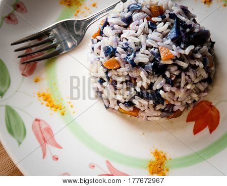 basmati rice with purple cabbage and carrots served on a white plate