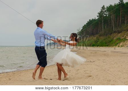 Bride And Groom Having Fun Together On The Beach
