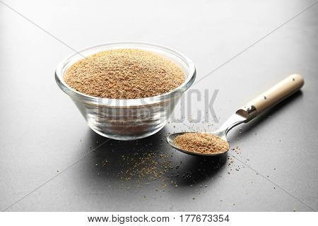 Glass bowl of bread crumbs on grey background