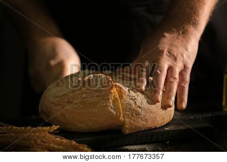 Man cutting bread on kitchen table, closeup