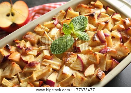 Tasty bread pudding with apples in baking dish, closeup