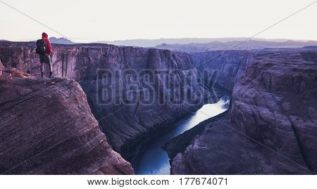 Male Hiker Overlooking Horseshoe Bend In Twilight, Arizona, Usa