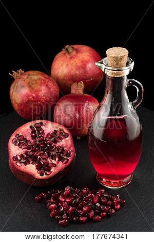 Pomegranates seeds and bottle of juice on black plate with black background