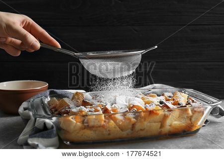 Woman decorating tasty bread pudding with sugar powder, closeup