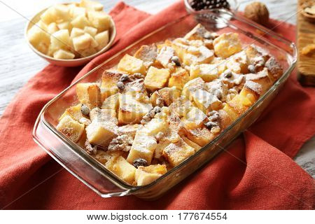 Bread pudding with raisins, walnuts and sugar powder in baking dish on table