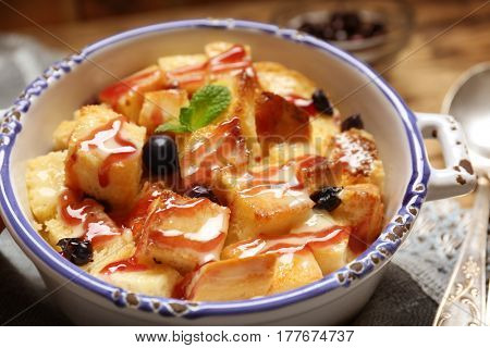 Delicious bread pudding with currant and jam in bowl