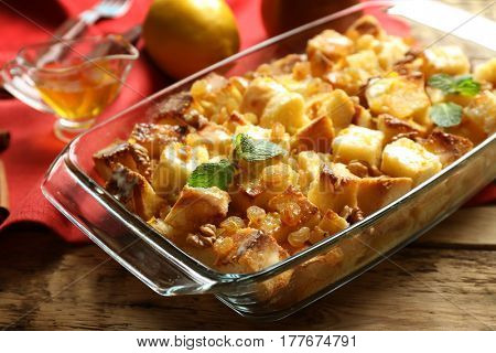 Delicious bread pudding with raisins in glass dish on table