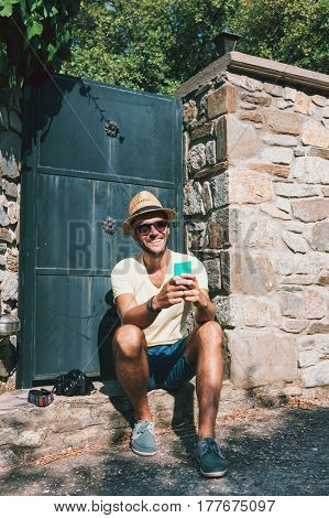 Young man using smartphone on a countryside road by the gate