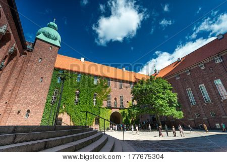 View on city hall (stadshuset) building in Stockholm Sweden Scandinavia Europe. Foreground with inner court and blue cloudy sky as background.