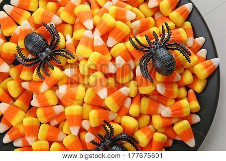 Plate with tasty Halloween candies, closeup