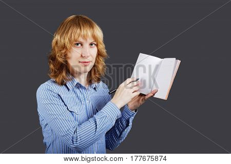 Red haired young woman holding an open notebook in one hand and pointing to it with a pen in the other hand. Isolated on grey background.