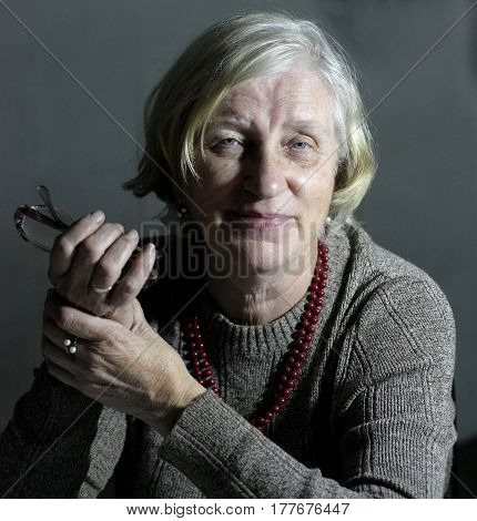 Senior woman with light gray hair with beads around her neck holds in right hand her glasses she dressed in gray knitted sweater.