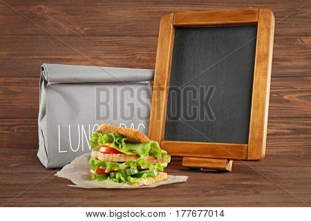 Lunch bag, small blackboard and sandwich on wooden background
