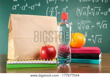 Lunch bag on wooden tabletop against chalkboard background