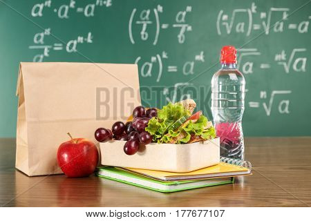 Lunch bag on wooden table against chalkboard background