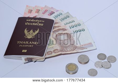 Thailand passport with insolated white background and copy space thai baht banknotes and coins
