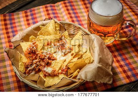 Straw bowl with nachos and meat served with glass of beer.