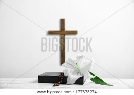 Composition of Holy Bible, lily, rosary and cross on light background