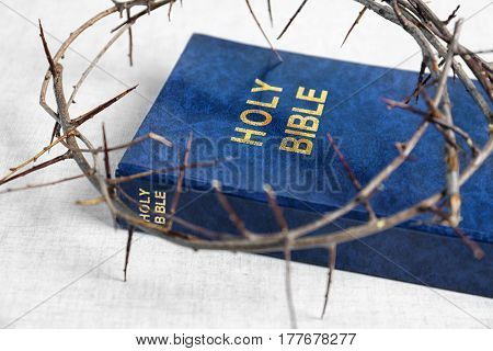 Holy Bible and crown of thorns on white fabric background