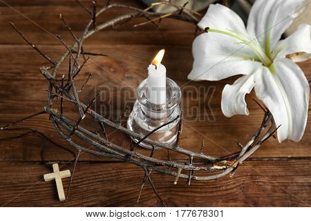 Candle in holder, crown of thorns, white lily and cross on wooden background