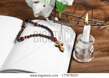 Opened blank book, candle with holder, rosary and crown of thorns on wooden table