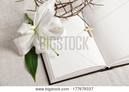 Blank opened book, lily and crown of thorns on white fabric background