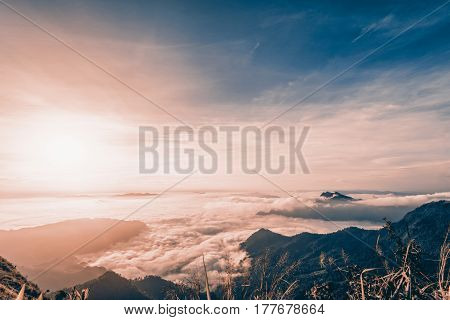 Vintage style in Sienna-Blue color two tone beautiful landscape nature of sunrise on peak mountain with cloud fog and sky in winter at Phu Chi Fa Forest Park Chiang Rai Province Thailand