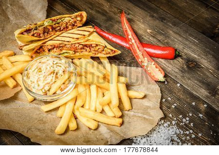 From above shot of burritos, French fries and cole slaw served on parchment.