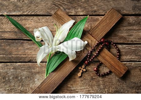 Cross and Easter white lily on wooden background