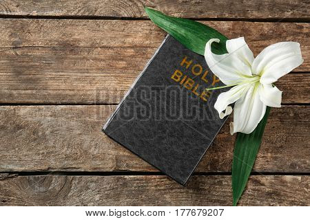 Holy Bible and Easter white lily on wooden background