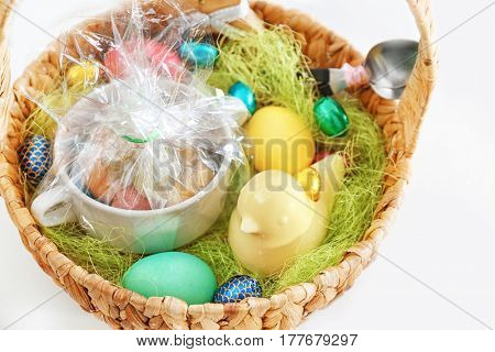 Easter basket with presents and decorations on white background