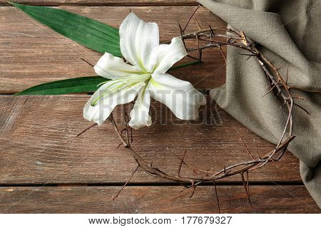 Crown of thorns and Easter white lily on wooden table