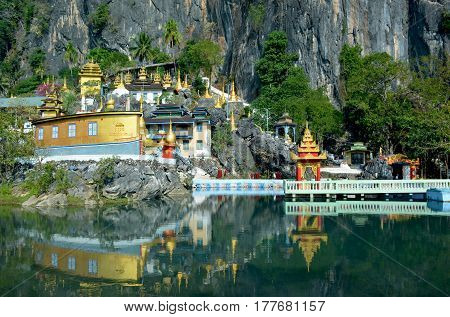 Bayin Nyi (Begyinni) Complex in Hpa-An Myanmar. Buddhist monastery and lots of golden stupas reflecting in the water of the sacred lake.
