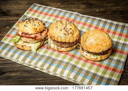 Three meat sliders served on checkered napkin.