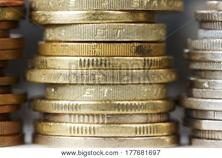 Coins in golden color stacked in a pile are shown up close