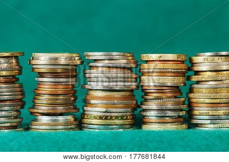 Coins stacked in five stacks can be seen against the background of green fabric