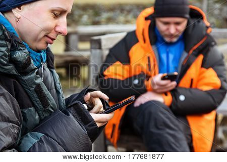 Male and Female Mountain Climbers in warm Down Jackets using mobile Telephones at Base Camp
