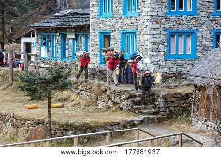 Porters of Himalaya Mountain expedition carrying heavy baskets and bags walking throw village. Kothey Lodge, Nepal, Solo-Khumbu region, November 2, 2016