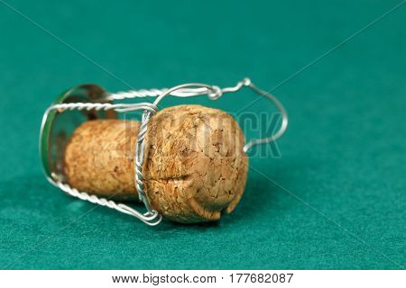 Cork of a sparkling wine is shown on a green background