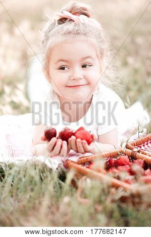 Smiling baby girl 3-4 year old eating fresh strawberry outdoors. Childhood.