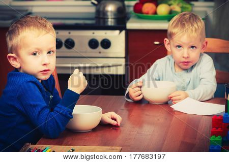 Morning routine in family healthy diet for children concept. Two boys kids eating breakfast together.