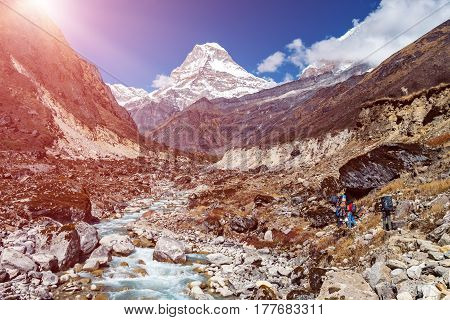 Mountain Valley View with high Peaks on Background and fast River Stream on Foreground Group of Hikers walking on left Sun shining