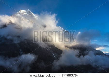 View of high Altitude Mountain Peak with Snow and Glaciers and sliced Clouds highlighted by evening Sunlight