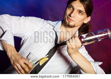 Alcohol liquor party relax concept. Partying barman makes cocktail. Young male bartender making drink holding glass bottle.