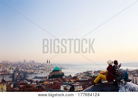 Morning View before Sunrise at large eastern City with Bosporus Channel and Mosque two People Man and Woman sitting on high Roof back to back