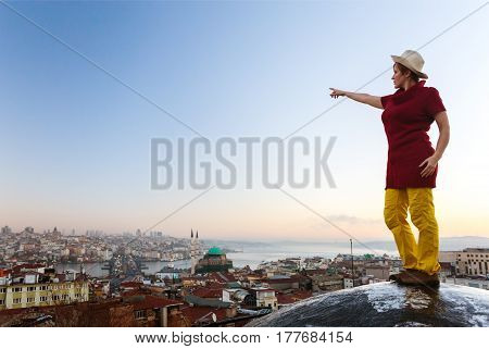 Morning View before Sunrise at large eastern City with Bosporus Channel and Mosque Woman pointing with Hand