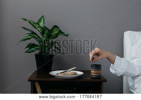 Female in Bed Stirring Cup of Coffee on Bedside Table