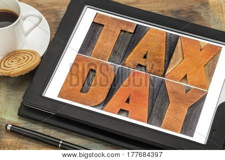 tax day concept - text in vintage letterpress wood type on a digital tablet with coffee