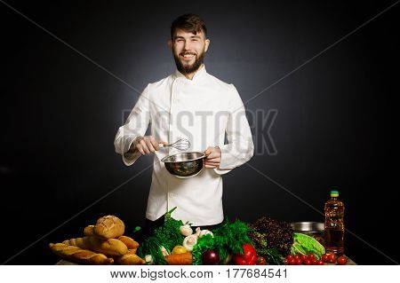 Cook chef with vegetables splah and black dark background. Food musical harmony. Chef juggling with vegetables and other food in the kitchen.