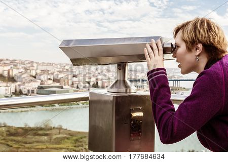 Female Tourist in casual clothing overlooking City Panorama throw Binoculars at popular Travel Spot